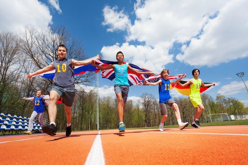 Jeunes participants multi-ethniques de course avec des drapeaux photo libre de droits