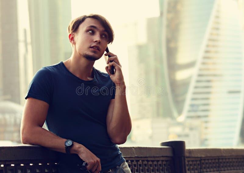 Jeunes pensant l'homme occasionnel marchant sur la rue et parlant sur m photos stock