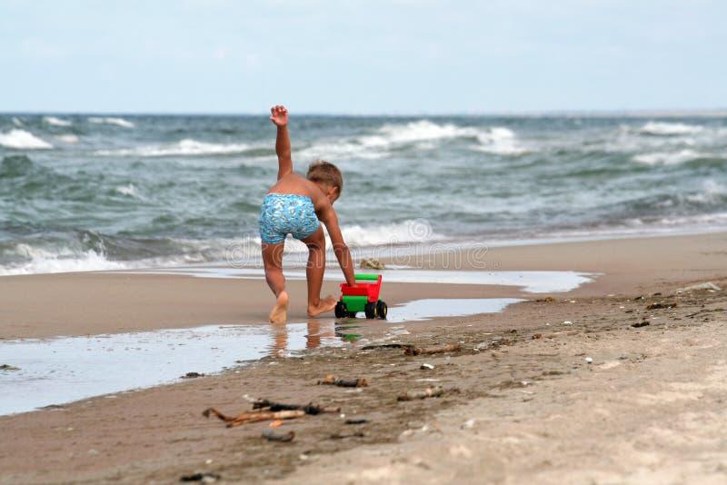 Jeunes pièces de garçon sur la plage image libre de droits