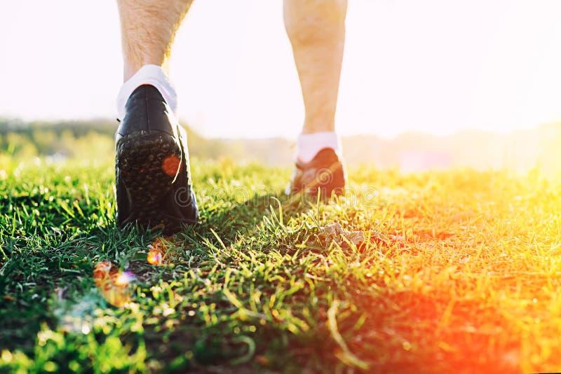 Jeunes pieds d'athlète fonctionnant en plan rapproché de parc sur la chaussure Séance d'entraînement masculine de trotteur d'athl photo libre de droits