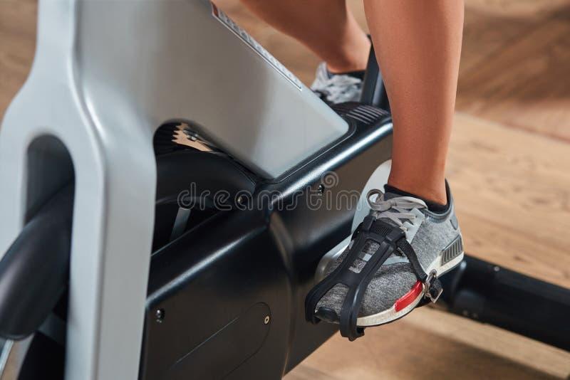 Jeunes pieds femelles s'exerçant et pédalant une bicyclette stationnaire photos libres de droits