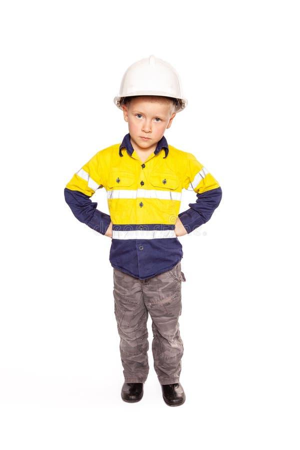 Jeunes poings caucasiens blonds de garçon sur le rôle de hanches jouant en tant que travailleur de la construction fâché dans sal photographie stock libre de droits