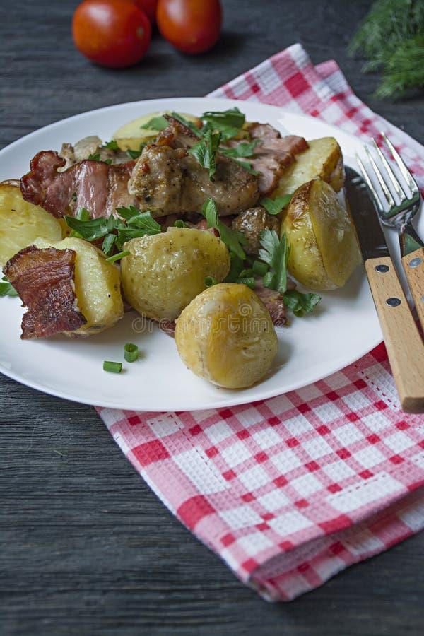Jeunes pommes de terre cuites au four avec de la viande et des légumes Fond en bois fonc? images stock