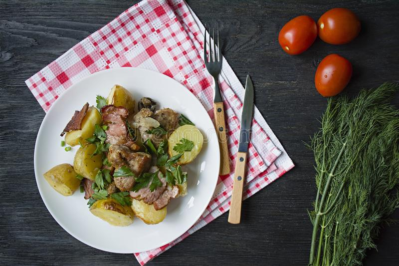 Jeunes pommes de terre cuites au four avec de la viande et des légumes Fond en bois fonc? photo stock