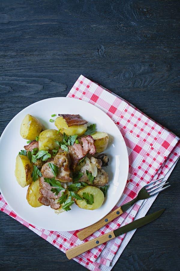 Jeunes pommes de terre cuites au four avec de la viande et des légumes Fond en bois fonc? photo libre de droits