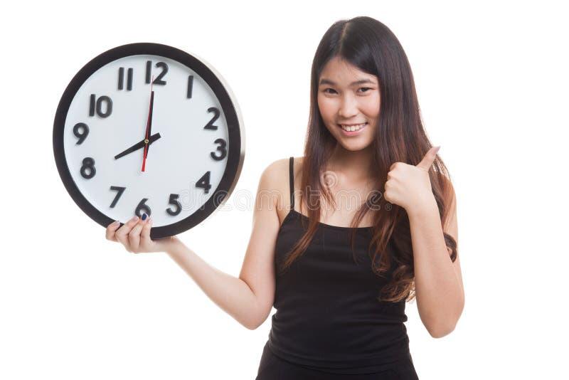 Jeunes pouces asiatiques de femme avec une horloge photos stock