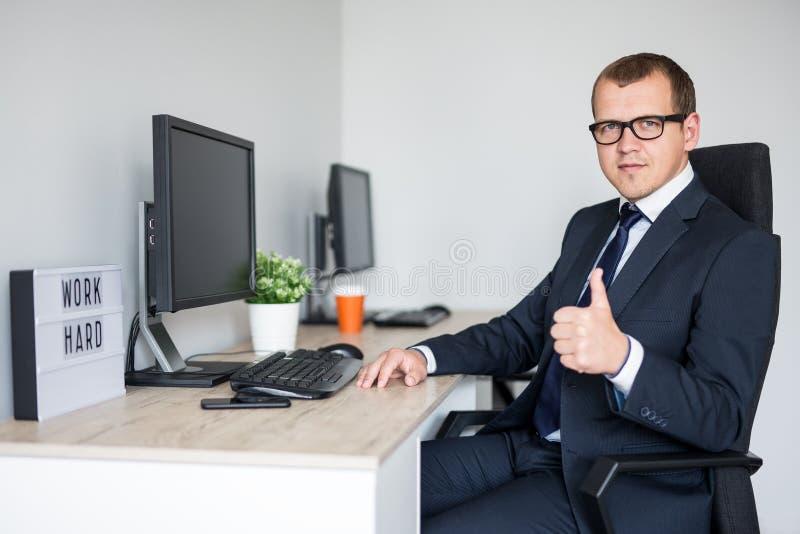 Jeunes pouces beaux d'homme d'affaires dans le bureau moderne image stock
