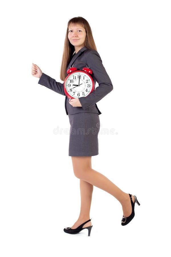 Jeunes prises de femme d'affaires dans son horloge d'alarme de mains image libre de droits