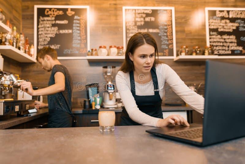 Jeunes propriétaires d'homme et de femme de couples de petit café moderne utilisant l'ordinateur portable pour le travail photographie stock libre de droits