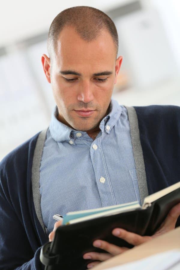 Jeunes rendez-vous d'écriture d'homme d'affaires à l'ordre du jour photographie stock libre de droits
