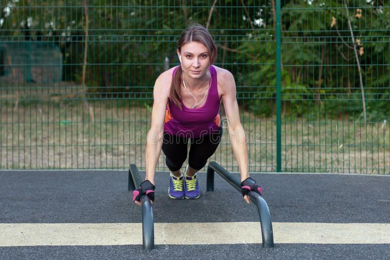Jeunes séances d'entraînement caucasiennes de femme sur l'au sol de sports de parc En position de planche de sports, vêtements de photo stock