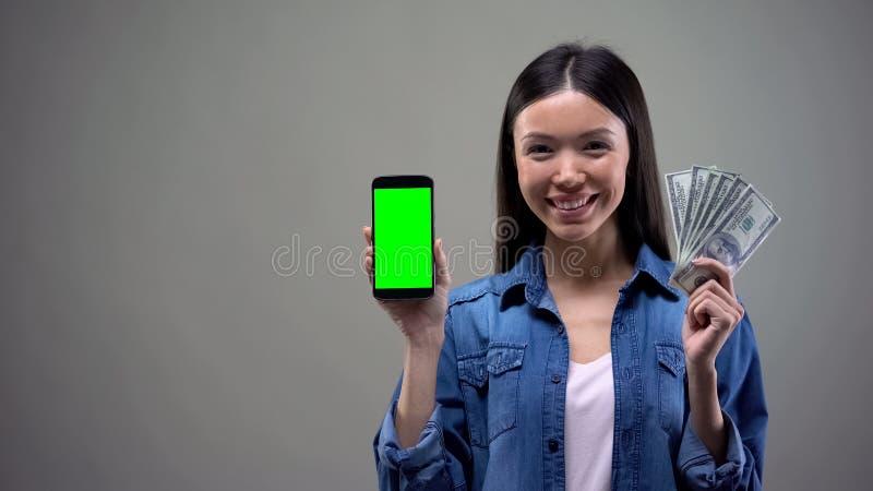 Jeunes smartphone de participation de femme et dollars asiatiques, d?veloppement d'applications informatique image stock