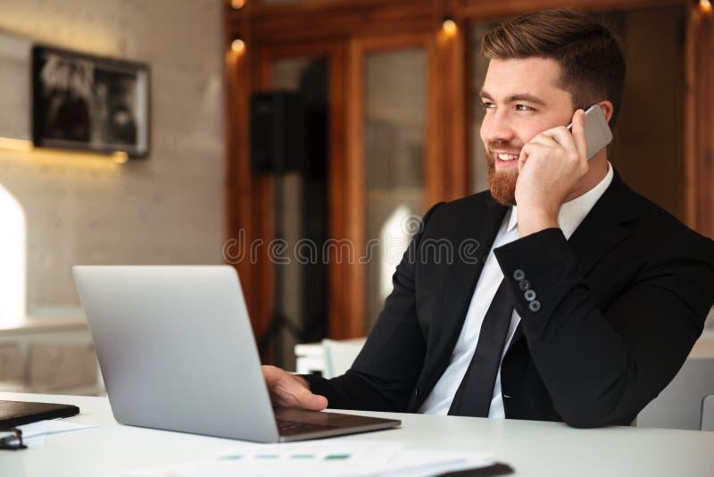 Jeunes smliing l'homme barbu d'affaires dans le costume noir parlant sur le mobi photo libre de droits
