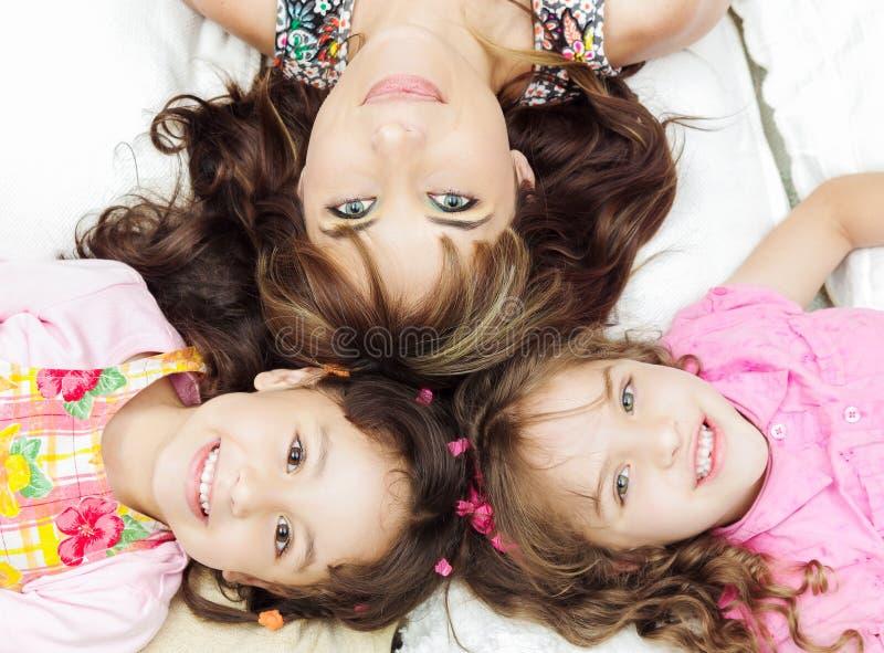 Jeunes soeurs hispaniques adorables avec le mensonge de mère image stock