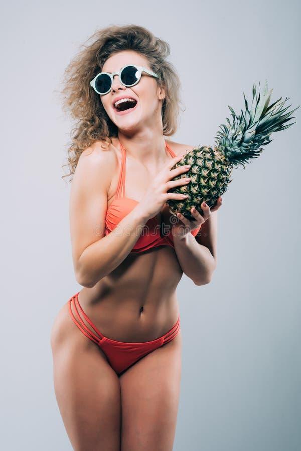 Jeunes souriant fille assez sexy dans des lunettes de soleil tenant l'ananas avec le corps de porfect d'isolement sur le fond bla images stock