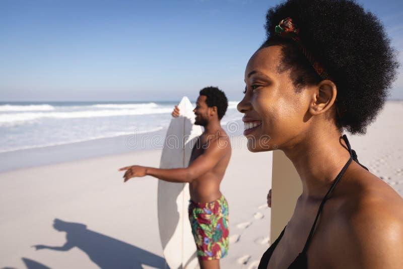 Jeunes surfers heureux se tenant avec des planches de surf sur la plage photographie stock libre de droits