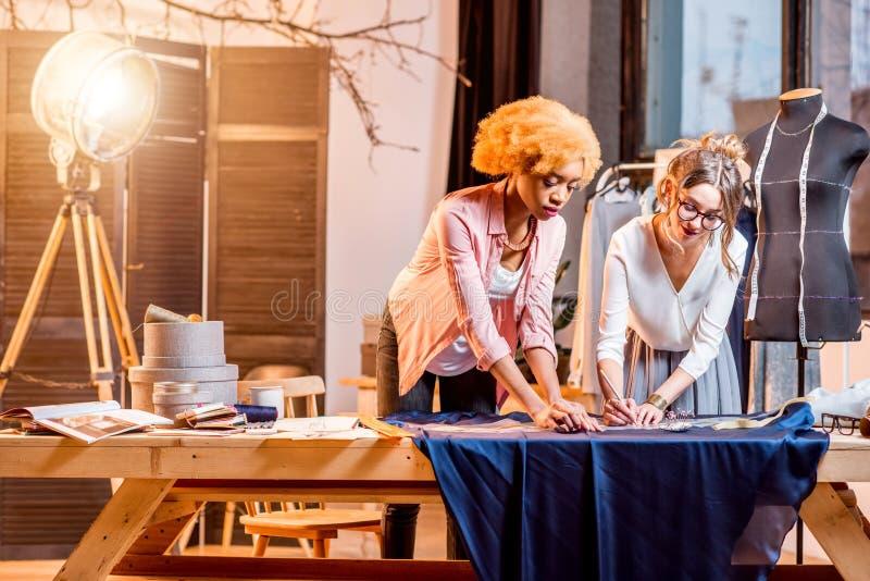 Jeunes tailleurs de femelle travaillant avec des vêtements image libre de droits