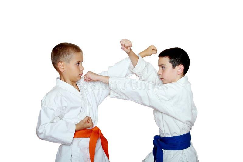 Jeunes techniques de karaté de train d'athlètes photo libre de droits