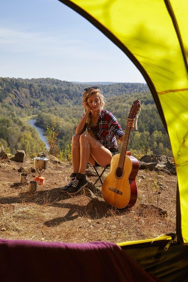 Jeunes touristes blondes de femme avec la guitare dans le camp sur la falaise au-dessus du ri photo stock