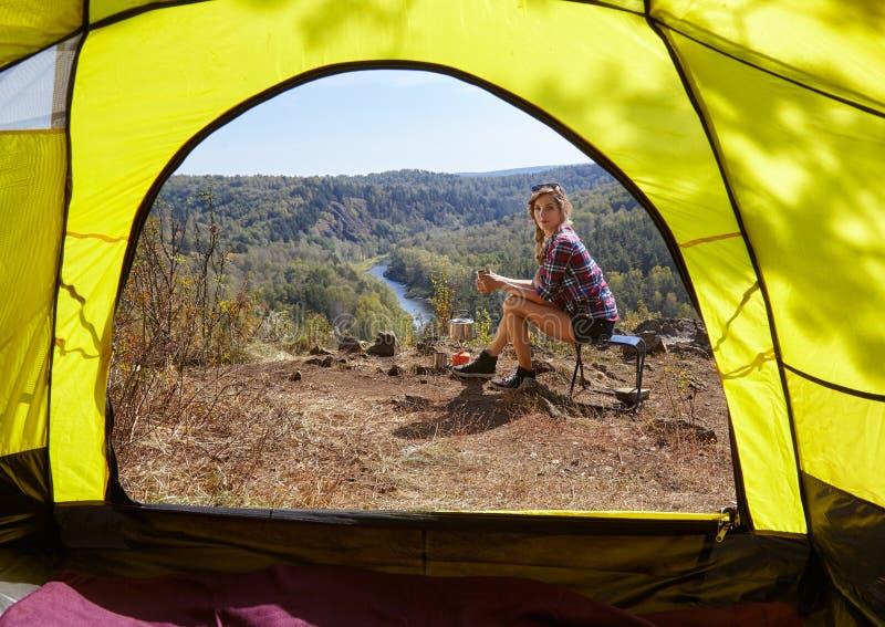 Jeunes touristes blondes de femme dans le camp sur la falaise au-dessus de la rivière et antérieur image stock