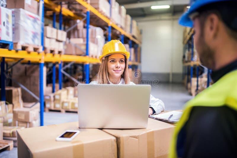 Jeunes travailleurs d'entrepôt avec l'ordinateur portable fonctionnant ensemble images libres de droits