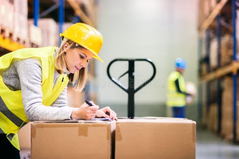 Jeunes travailleurs travaillant dans un entrepôt photographie stock libre de droits