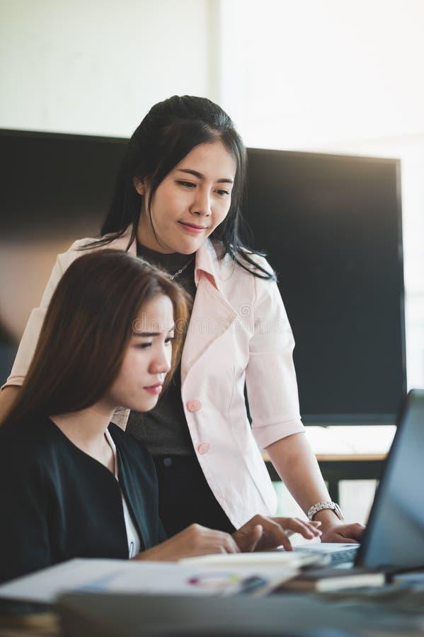 Jeunes travailleuses asiatiques travaillant ensemble dans le bureau photographie stock