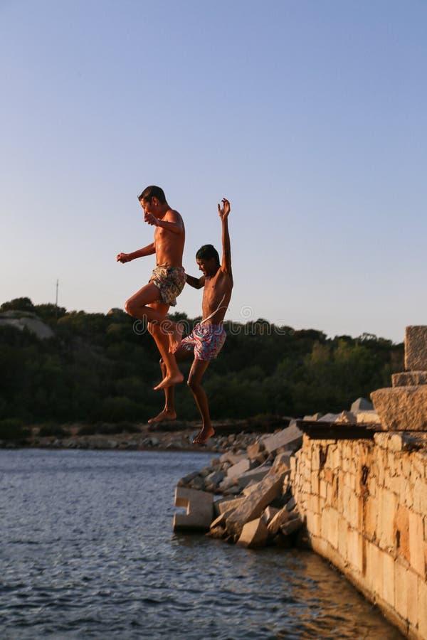 Jeunes types comme qui à sauter dans la mer photographie stock libre de droits