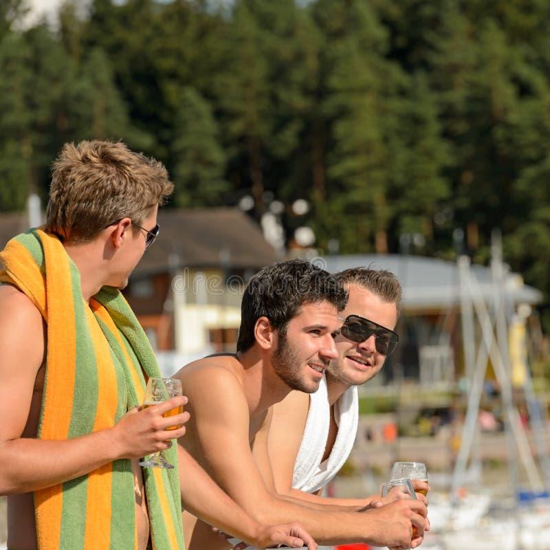 Jeunes types à la bière potable de plage images stock
