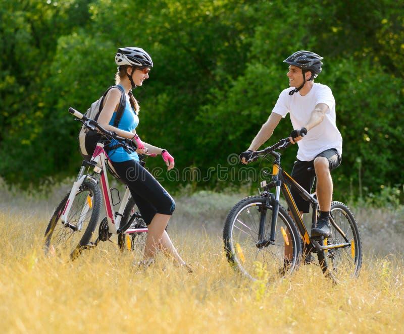 Jeunes vélos de montagne heureux d'équitation de couples extérieurs images libres de droits