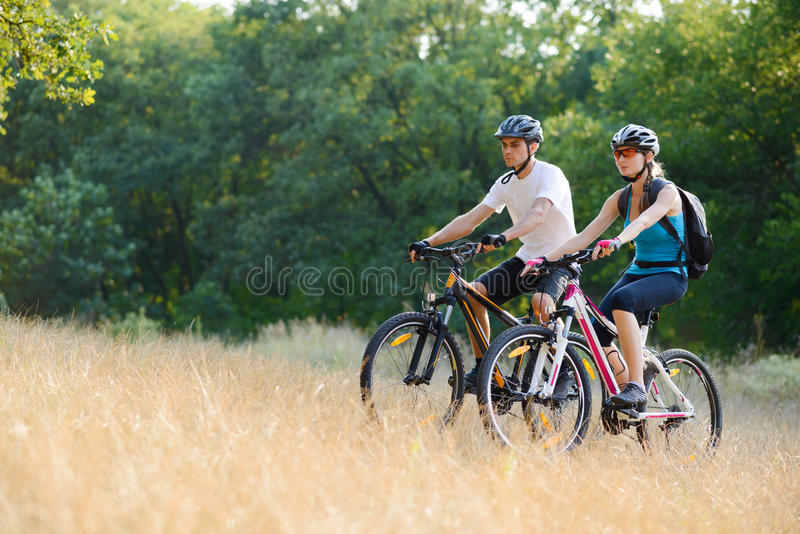 Jeunes vélos de montagne heureux d'équitation de couples extérieurs images stock