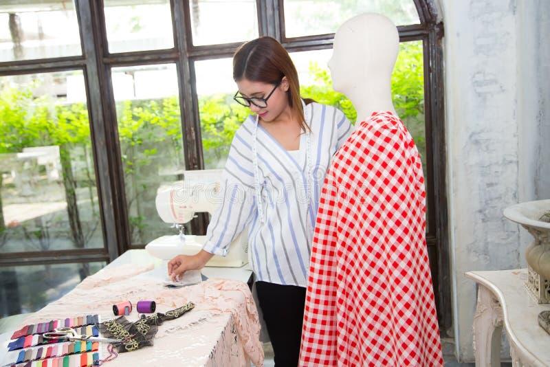 Jeunes vêtements workingdesigning femelles de couturier pour le puppe photographie stock