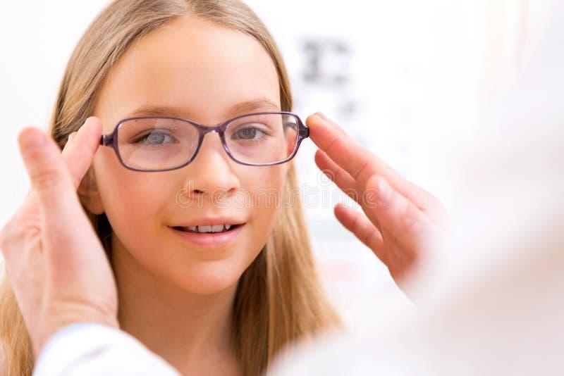 Jeunes verres de essai de petite fille à l'opticien photographie stock