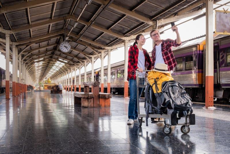 Jeunes voyageurs heureuxde coupleensemble des vacances prenant un selfie au téléphone à la station de train, concept de voyage image libre de droits