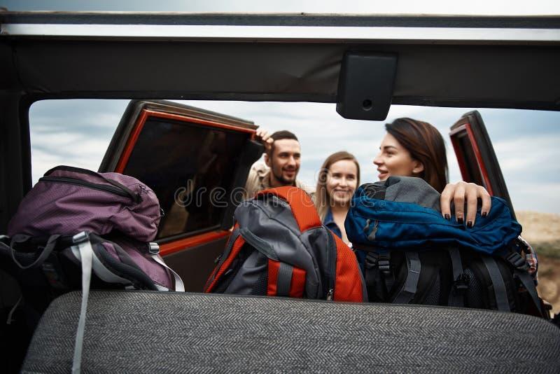 Jeunes voyageurs positifs obtenant leurs sacs à dos de la voiture photos stock