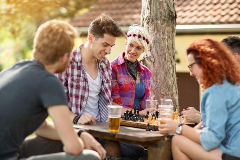 Jeunesse ayant l'amusement jouant des échecs en bois photo libre de droits