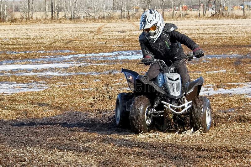 Jeunesse faisant des butées toriques dans la boue sur son quadruple photos libres de droits