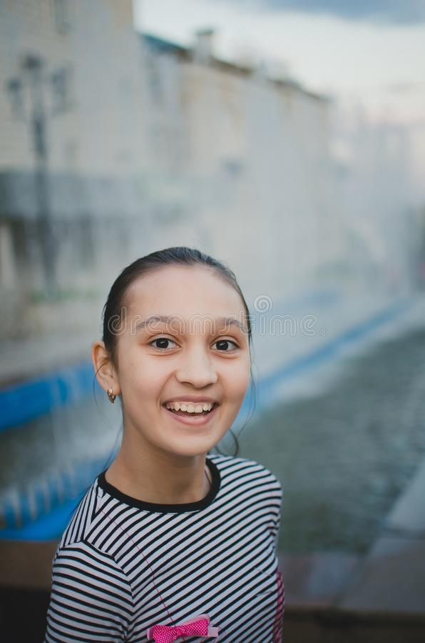 Jeunesse heureuse de fille de l'adolescence et journée de printemps ensoleillée, fontaine proche extérieure urbaine images libres de droits