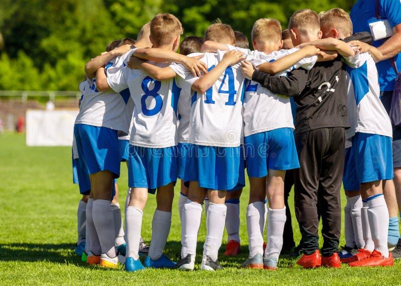 Jeunesse Team Huddling du football avec l'entra?neur Jeune collecte heureuse de footballeurs de gar?ons photo libre de droits