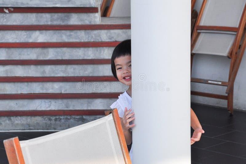 Jeux asiatiques de petite fille de portrait chercher et se cacher derrière le courrier de ciment image libre de droits