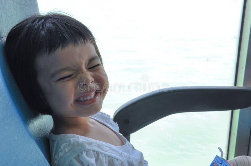 Jeux asiatiques de petite fille de portrait chercher et se cacher derrière le courrier de ciment images libres de droits