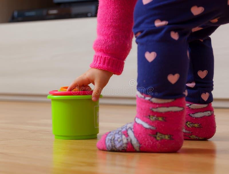 Jeux de bébé d'enfant en bas âge avec les tasses colorées image libre de droits
