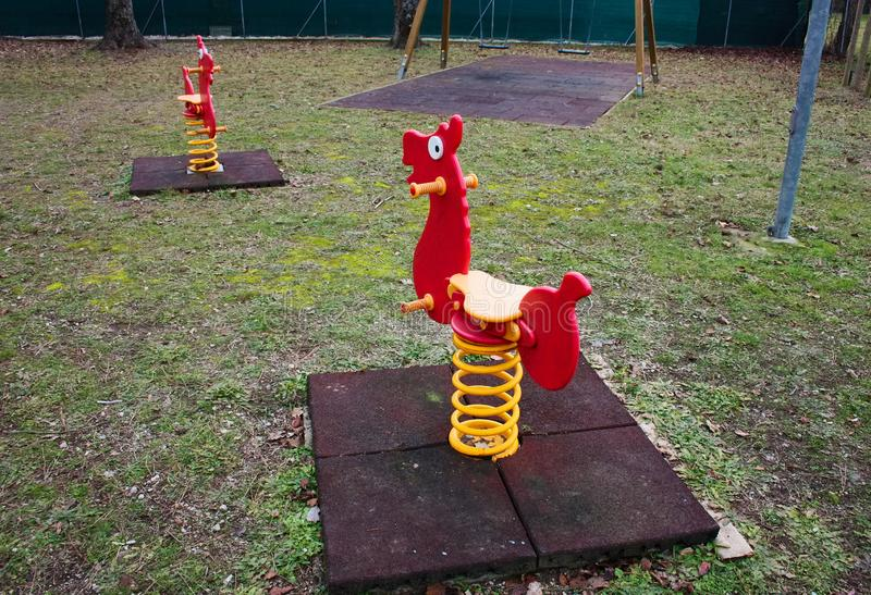 Jeux de basculage pour de petits enfants oscillations rouges formées comme de petits chevaux Terrain de jeu abandonné photo libre de droits
