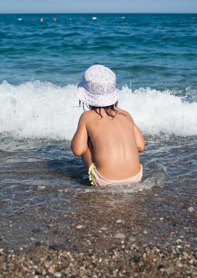 Jeux de fille avec des vagues image libre de droits