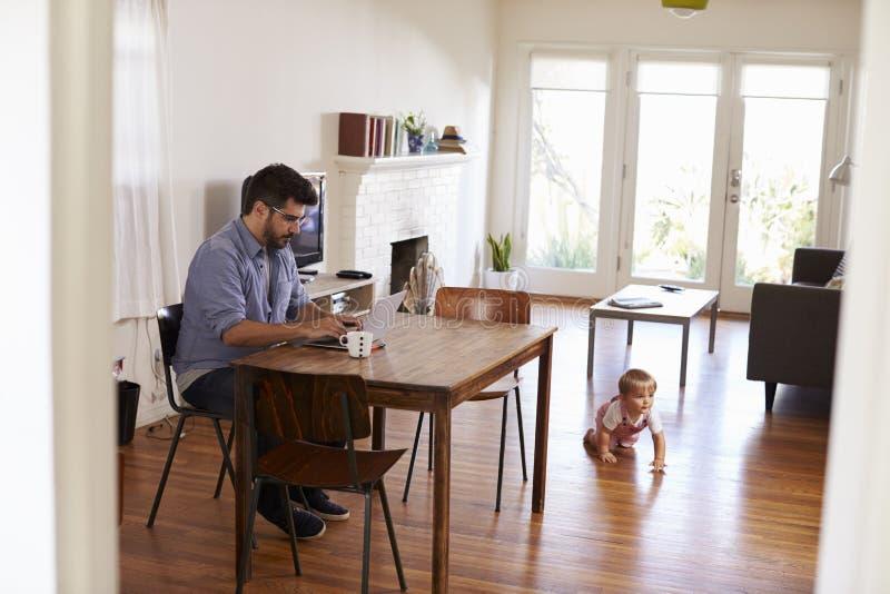 Jeux de fils de bébé d'Uses Laptop Whilst de père sur le plancher image stock