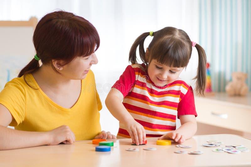 Jeux de jeune femme avec le jeu éducatif d'enfant image stock