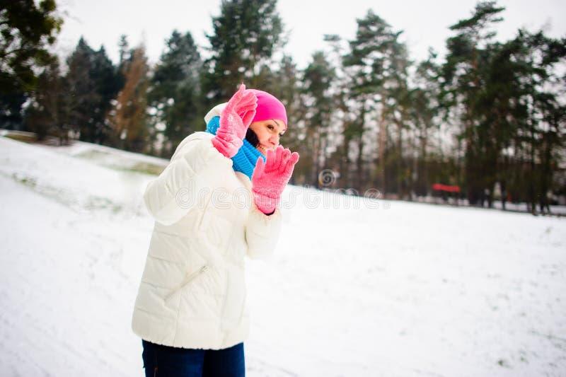 Jeux de jeune femme avec quelqu'un dans les boules de neige image libre de droits