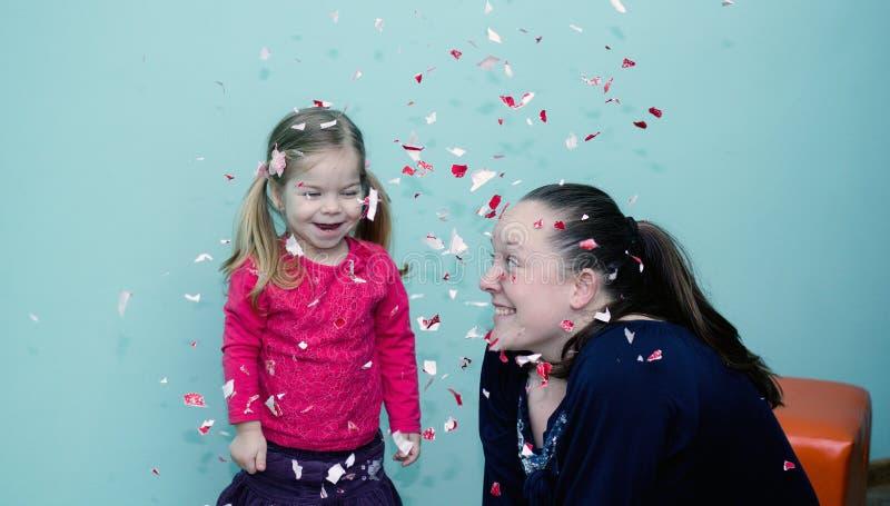 Jeux de jeunes femmes avec des confettis avec la petite fille photos stock