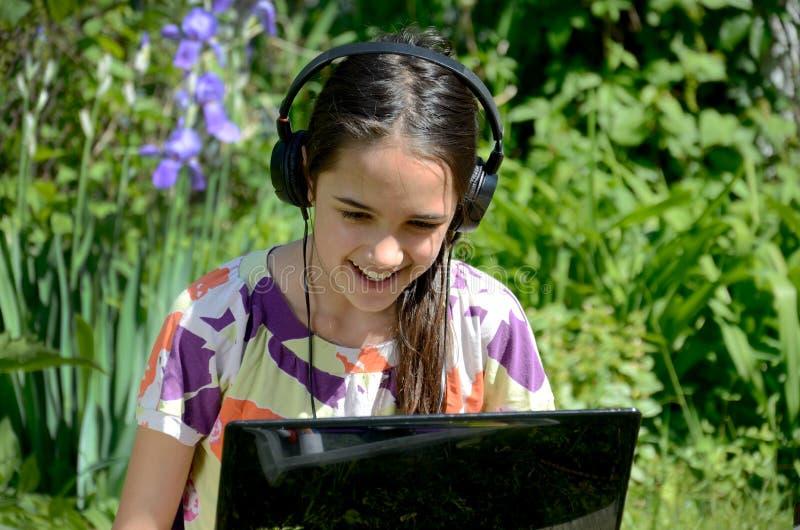 Jeux de petite fille sur un ordinateur portable dans le jardin photographie stock
