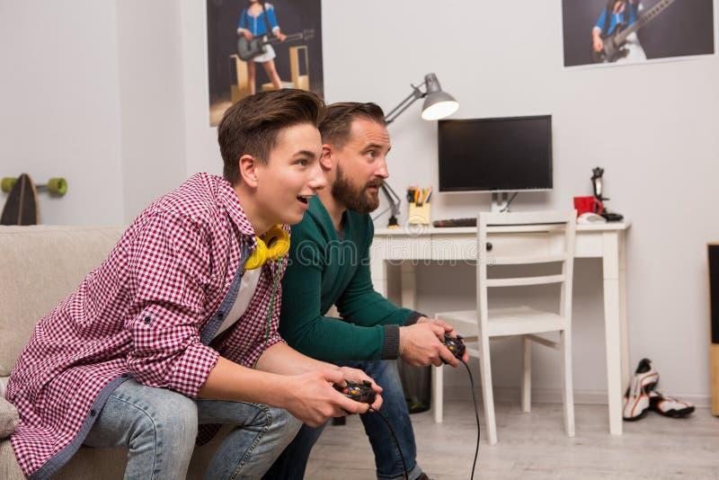 Jeux palying de console d'adolescent avec le père images libres de droits